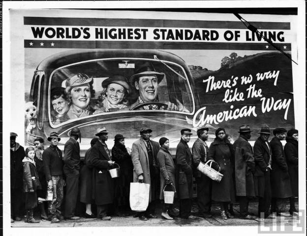 Famous image of African American flood victims lined up to get food & clothing fr. Red Cross relief station in front of billboard ironically extolling WORLD'S HIGHEST STANDARD OF LIVING/ THERE'S NO WAY LIKE THE AMERICAN WAY.
